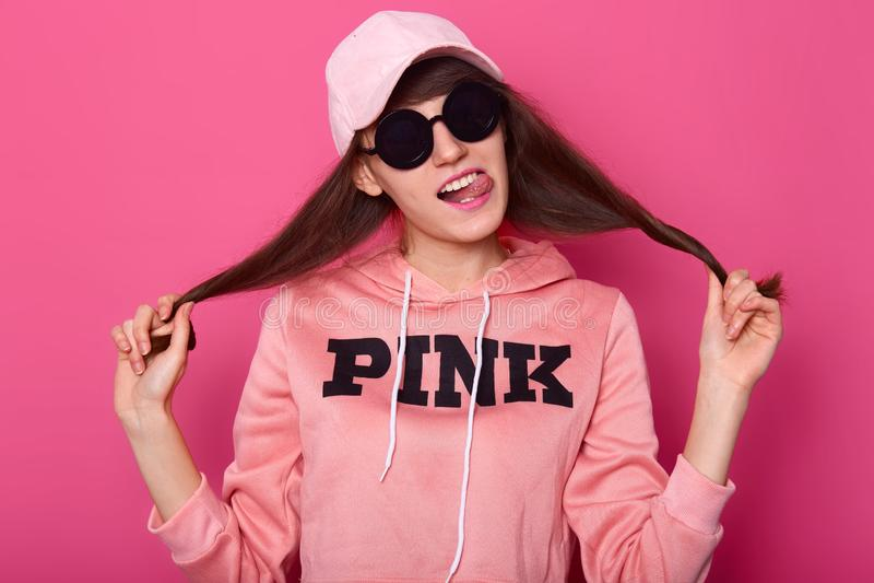 Porträt des netten netten attraktiven Mädchens, das ihre Haarnebenwirkungen zieht, trägt verkürzten Hoodie, Kappe und stilvolle s stockbilder