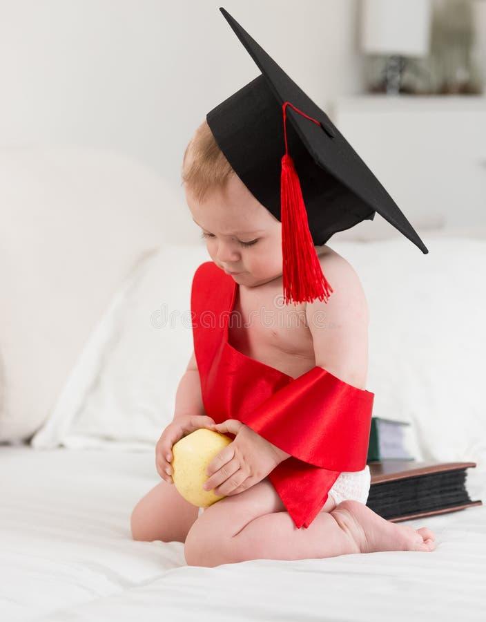 Porträt des netten Babys in der Staffelungskappe, die Apfel hält Konzept O lizenzfreie stockfotografie