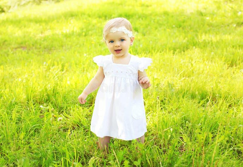 Porträt des netten Babys gehend auf das Gras stockbild