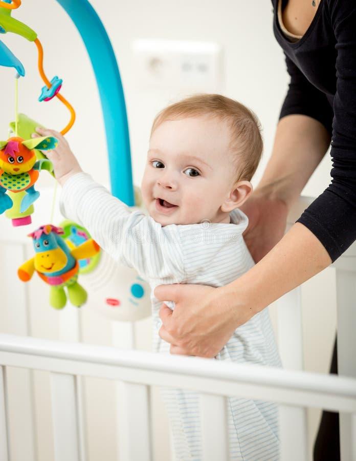 Porträt des netten Babys spielend mit Karussell in der Krippe lizenzfreie stockfotografie