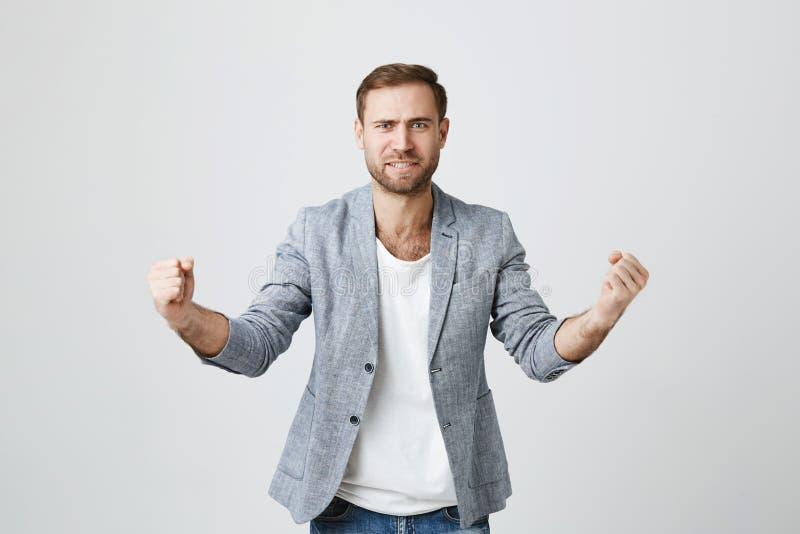 Porträt des netten blauäugigen attraktiven europäischen unrasierten Mannes, der aufgeregt und froh ist, Sieg zu erzielen, preßt z lizenzfreies stockbild
