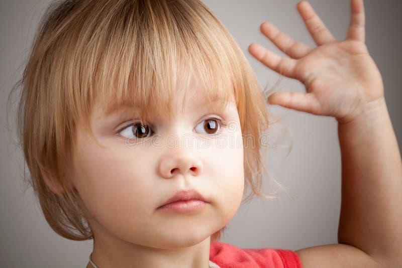 Porträt des netten blonden Babys mit der Hand herauf Geste stockfoto