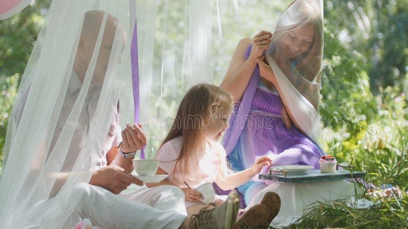 Porträt des netten blonden kleinen Mädchens mit Familie im Park stockbilder