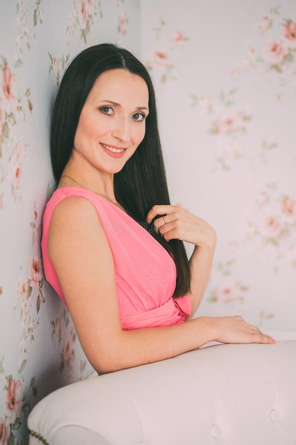 Porträt des netten Brunettemädchens im rosa Kleid, untersuchend die Kamera Pastellfarbeton lizenzfreie stockfotografie