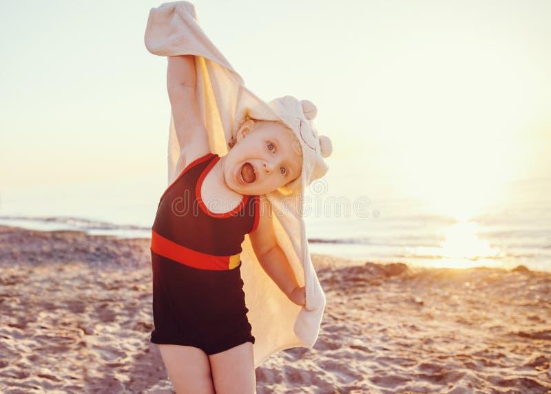 Porträt des netten entzückenden glücklichen lächelnden kleinen Mädchens des Kleinkindes mit Tuch auf dem Strand, der die Haltungs lizenzfreie stockfotos