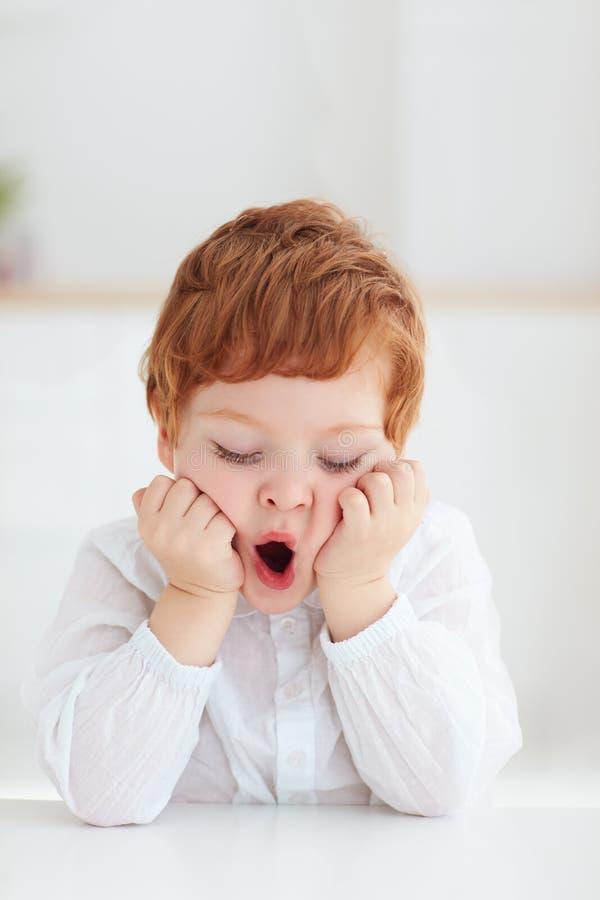 Porträt des netten gebohrten Vorschülers, gähnendes Baby beim Sitzen am Tisch stockfoto