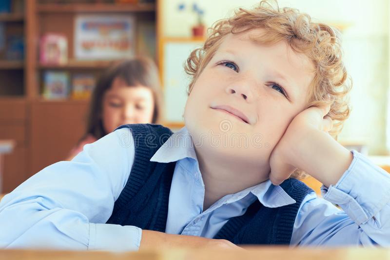Porträt des netten gelockten durchdachten Schülers, der am Schreibtisch und am Träumen sitzt lizenzfreie stockbilder