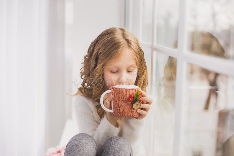 Porträt des netten glücklichen kleinen Mädchens, das auf Fensterbrett sitzt lizenzfreie stockbilder