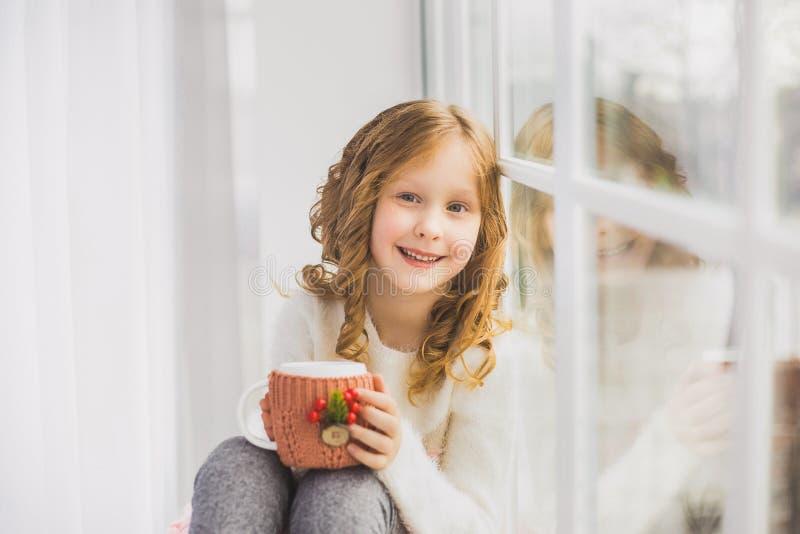 Porträt des netten glücklichen kleinen Mädchens, das auf Fensterbrett sitzt lizenzfreie stockfotos