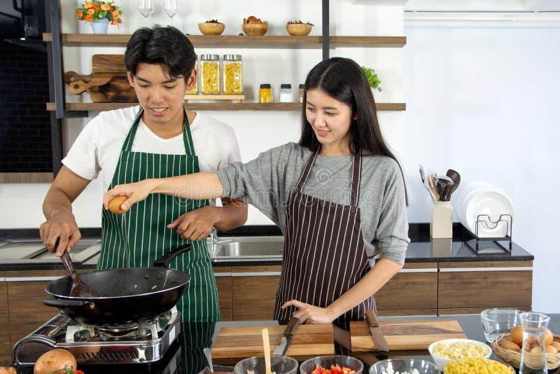 Porträt des netten glücklichen Paars im Schutzblech, das Frühstücksdame vorbereitet, fügen Ei in die Wanne hinzu, die mit Bestand stockfoto