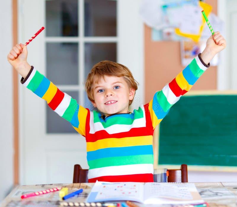 Porträt des netten glücklichen Schulkinderjungen zu Hause, der Hausarbeit macht Kleines Kinderschreiben mit bunten Bleistiften, z lizenzfreie stockfotografie