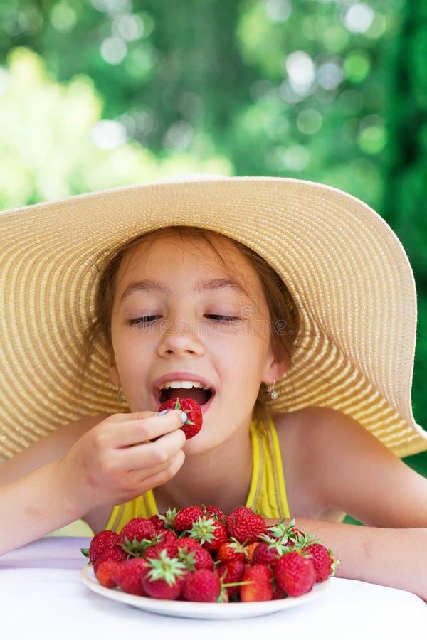 Porträt des netten jugendlich Mädchens im Großen Hut isst Erdbeere in SU lizenzfreie stockfotos