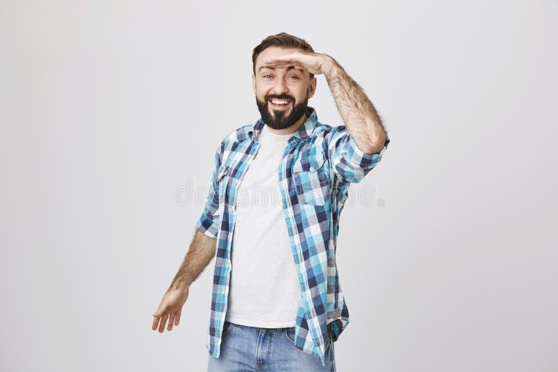 Porträt des netten jungen Erwachsenen, der weit weg mit der Hand auf seiner Stirn, breit lächelnd bei der Stellung über Grau scha lizenzfreie stockfotografie