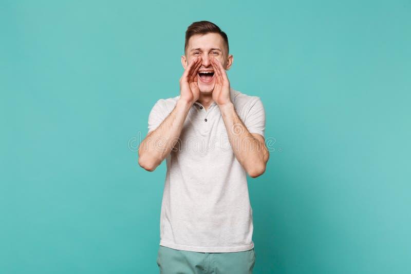 Porträt des netten jungen Mannes in der zufälligen Kleidung schreiend mit den Händen nahe dem Mund lokalisiert auf blauer Türkisw lizenzfreie stockbilder