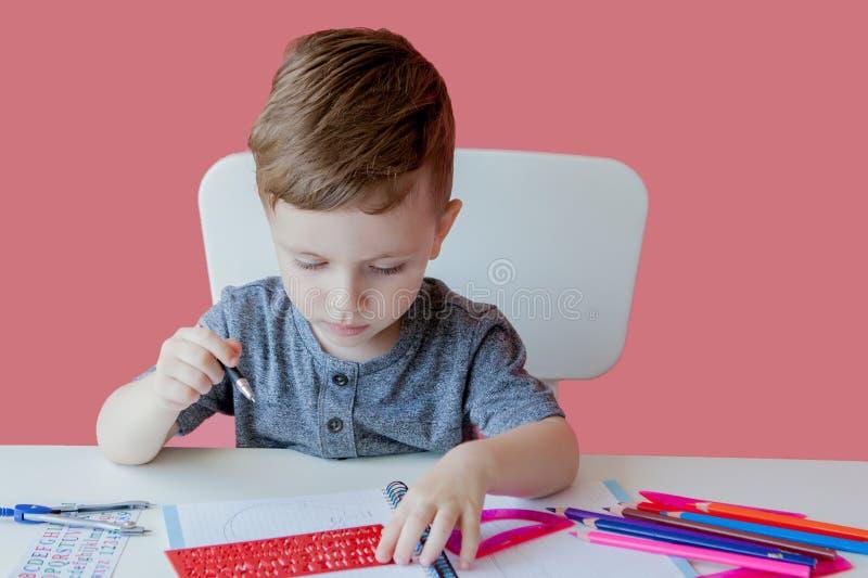 Porträt des netten Kinderjungen zu Hause, der Hausarbeit macht Wenig starkes Kind, das mit buntem Bleistift, zuhause schreibt gru stockfotografie