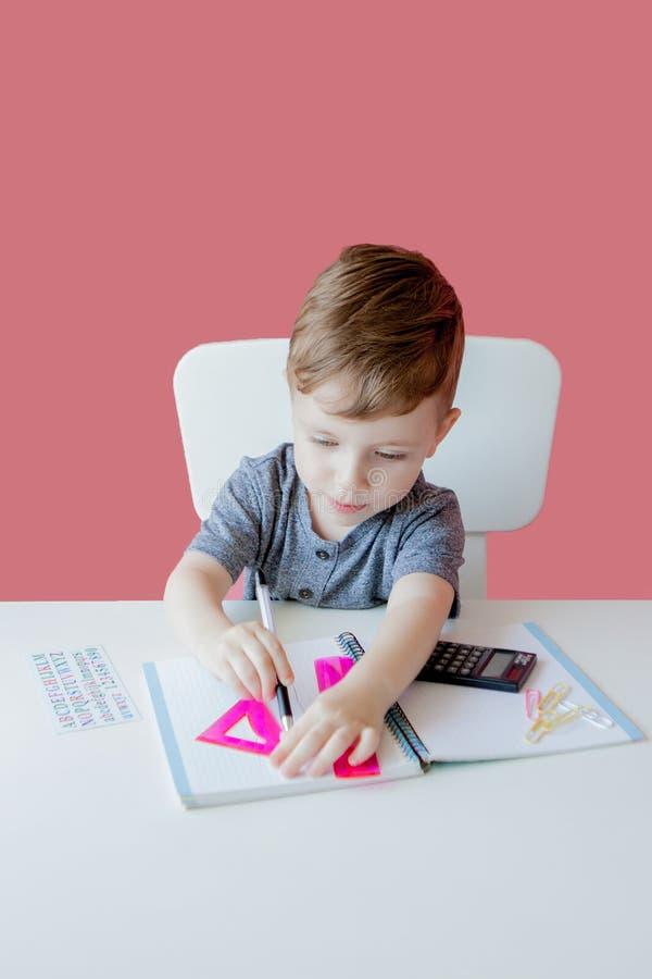 Porträt des netten Kinderjungen zu Hause, der Hausarbeit macht Wenig starkes Kind, das mit buntem Bleistift, zuhause schreibt gru stockbilder