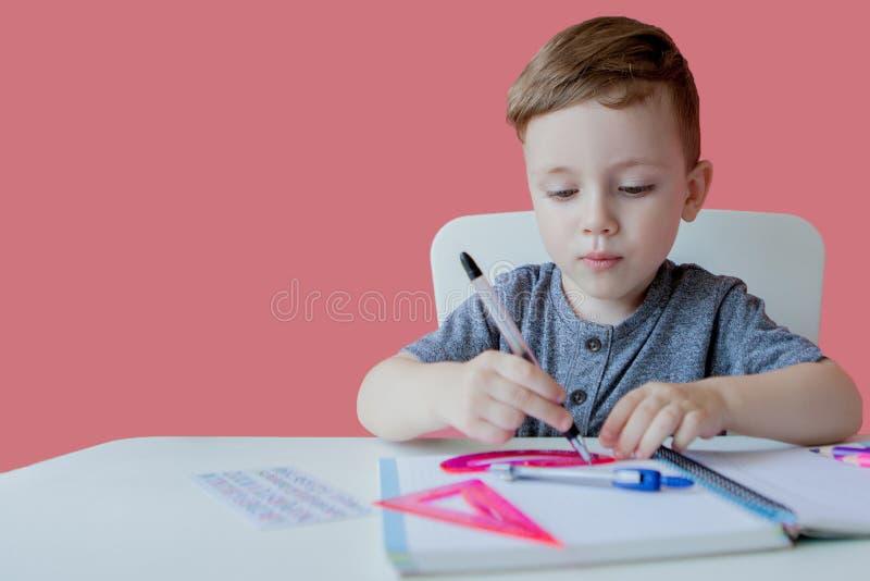 Porträt des netten Kinderjungen zu Hause, der Hausarbeit macht Wenig starkes Kind, das mit buntem Bleistift, zuhause schreibt gru lizenzfreie stockfotografie