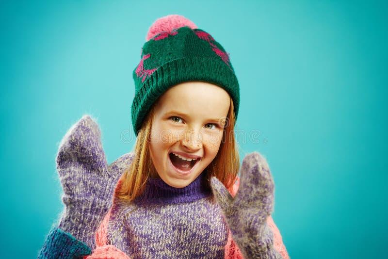 Porträt des netten Kindermädchens trägt Winterhandschuhe, warme Strickjacke, Hut mit Pompom und openwork Kapschal auf Blau lizenzfreies stockbild