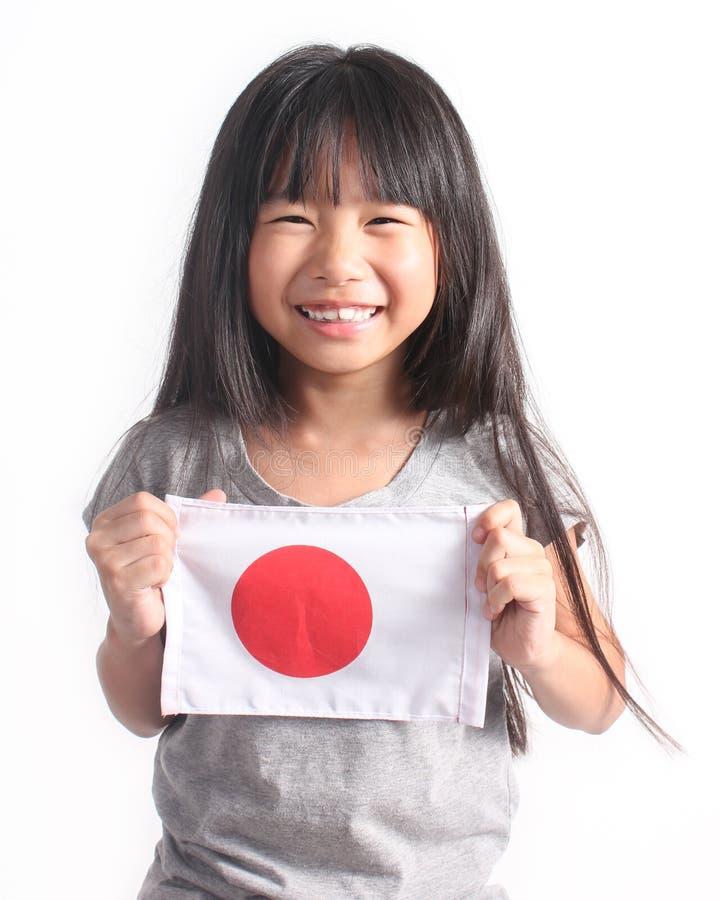 Porträt des netten kleinen asiatischen Mädchens, das japanische Flagge hält lizenzfreie stockfotos