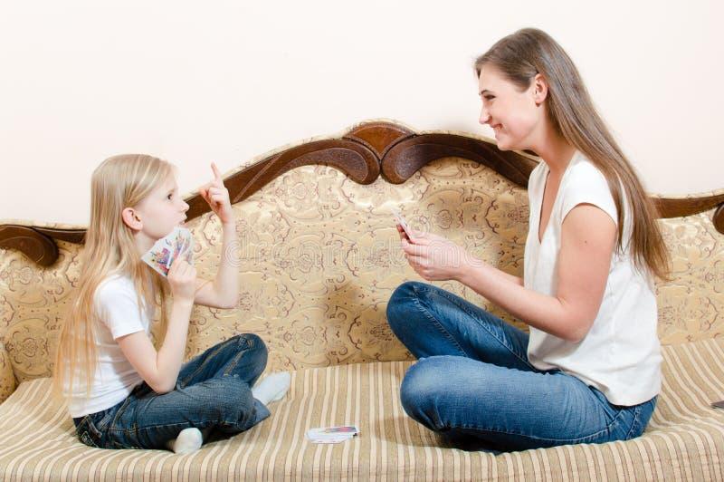 Porträt des netten kleinen blonden Kindermädchens und der Frau des schönen Brunette jungen, die glückliche lächelnde Spielkarten  stockfoto