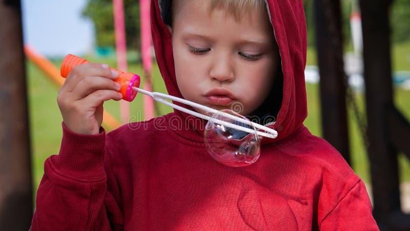 Porträt des netten kleinen Jungen, der Seifenblasen macht lizenzfreie stockbilder