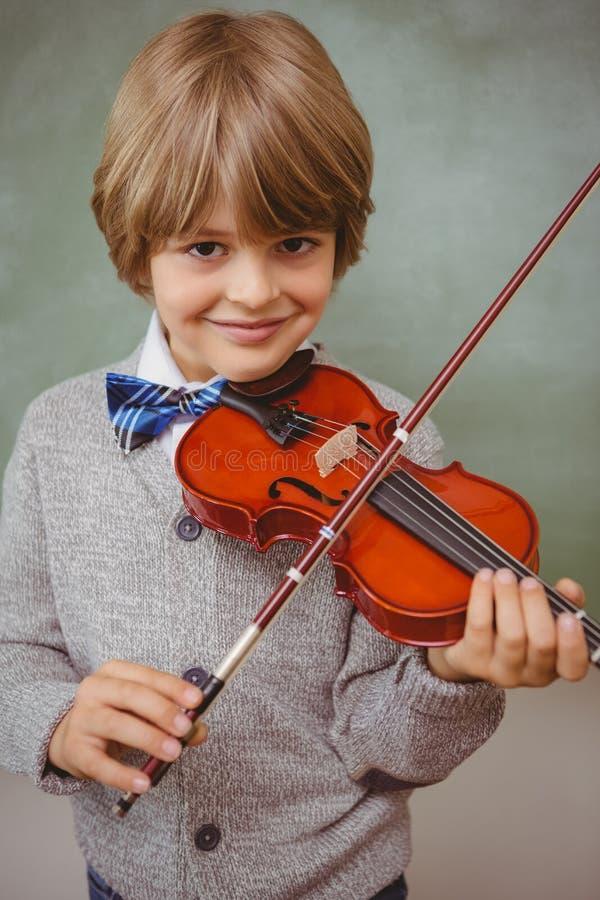 Porträt des netten kleinen Jungen, der Violine spielt stockfotografie