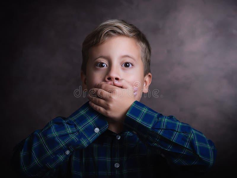Porträt des netten kleinen Jungen schloss Mund mit seiner Hand, Atelieraufnahme lizenzfreies stockfoto