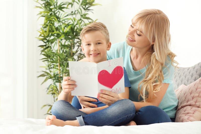 Porträt des netten kleinen Jungen und seiner Mutter mit handgemachter Karte im Schlafzimmer lizenzfreie stockbilder