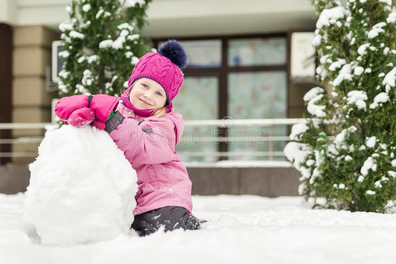 Porträt des netten kleinen Mädchens, das smowman macht am hellen Wintertag Entzückendes Kind, das draußen mit Schnee spielt lusti stockbilder