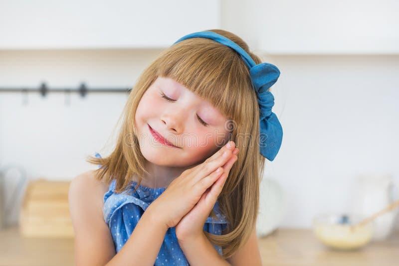 Porträt des netten kleinen Mädchens im blauen Kleid schläft auf einer Küche stockbild