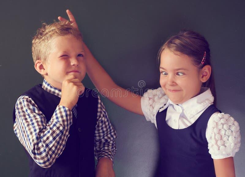 Porträt des netten kleinen Mädchens mit dem spielenden Freund und im Klassenzimmer herum täuschen stockfotografie