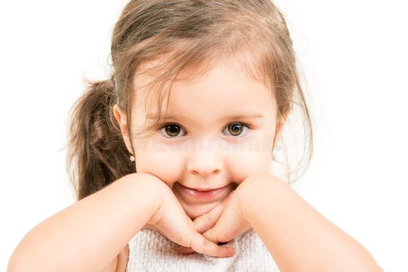 Porträt des netten kleinen Mädchens mit den Händen unter dem Kinn lokalisiert lizenzfreies stockbild