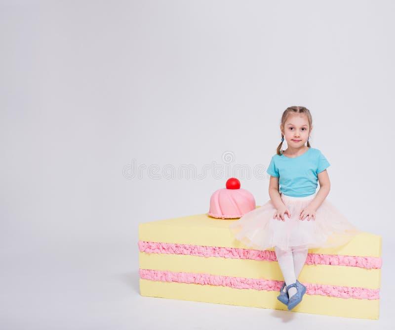 Porträt des netten kleinen Mädchens mit großem Kuchen- und Kopienraum über Weiß stockfoto