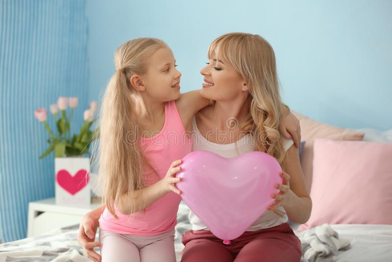 Porträt des netten kleinen Mädchens und ihrer Mutter mit Ballon zu Hause lizenzfreies stockbild