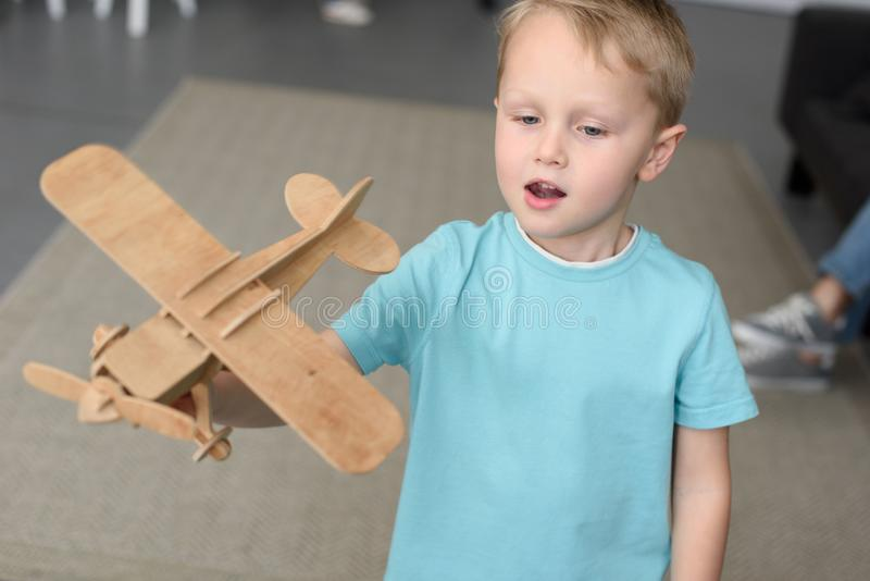 Porträt des netten Kleinkindes mit hölzernem flachem Spielzeug in der Hand lizenzfreie stockbilder