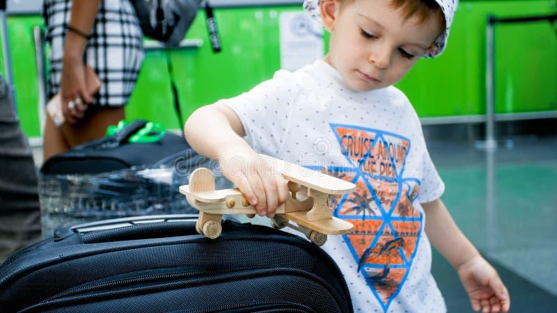 Porträt des netten Kleinkindjungen, der mit hölzernem Spielzeugflugzeug in der Abfertigungslinie spielt lizenzfreie stockfotografie