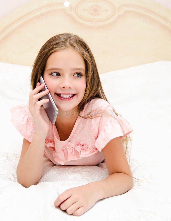 Porträt des netten lächelnden Kindes des kleinen Mädchens, das durch Handy Smartphone liegt auf dem Bett nennt lizenzfreie stockfotografie