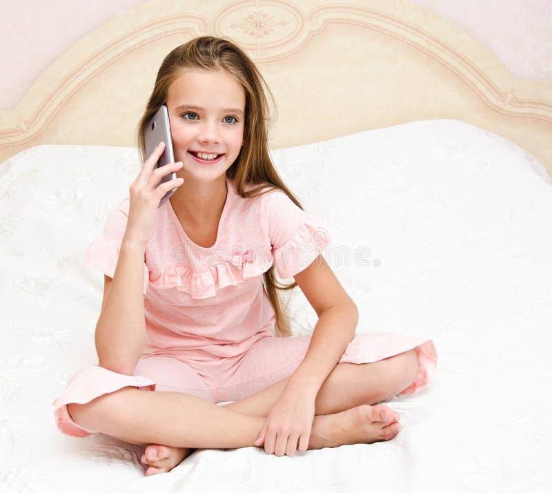 Porträt des netten lächelnden Kindes des kleinen Mädchens, das durch Handy Smartphone sitzt auf dem Bett nennt stockfotografie