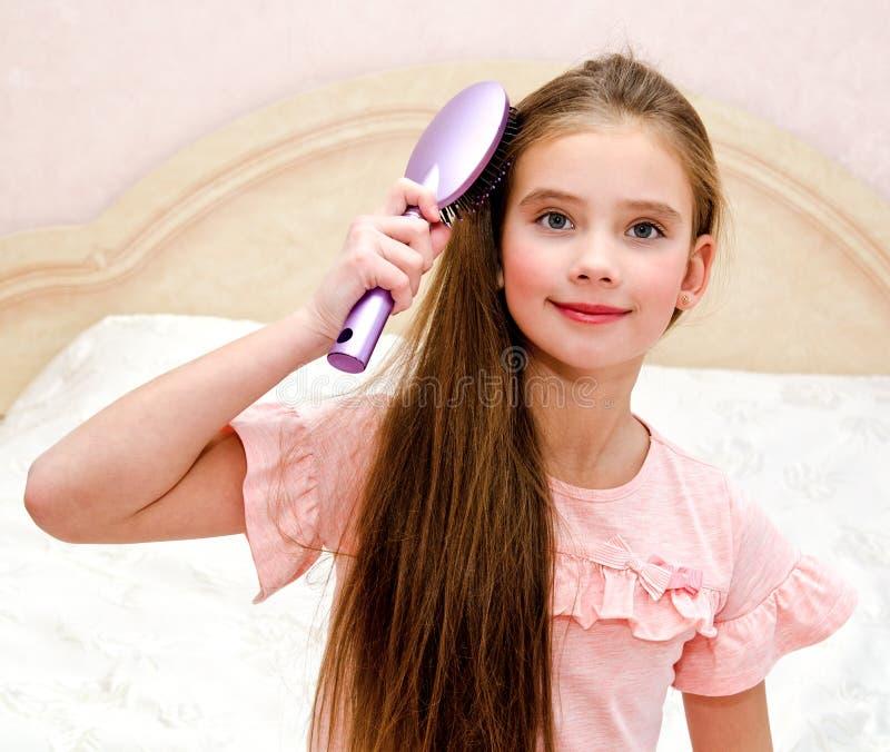 Porträt des netten lächelnden Kindes des kleinen Mädchens, das ihr Haar bürstet stockbilder