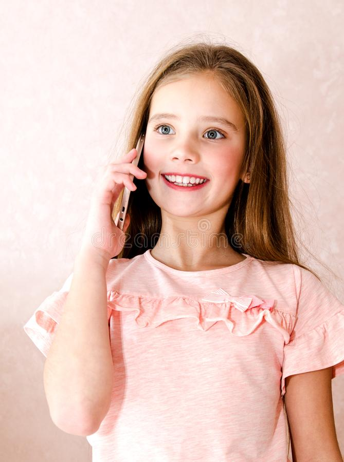 Porträt des netten lächelnden kleinen Mädchens nennend durch Handy smar stockfotografie