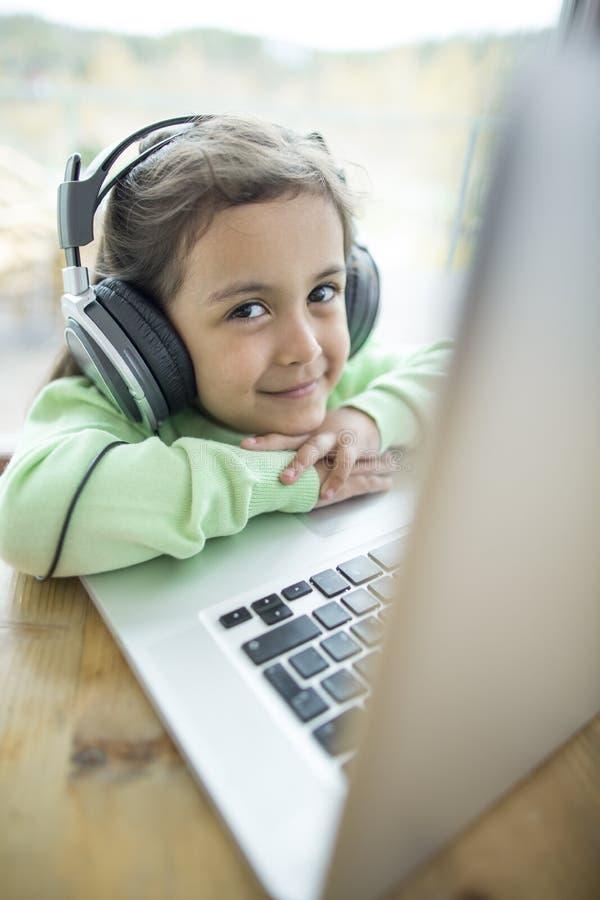 Porträt des netten Mädchens hörend Musik auf Kopfhörern bei Laptop zu Hause verwenden lizenzfreie stockfotos