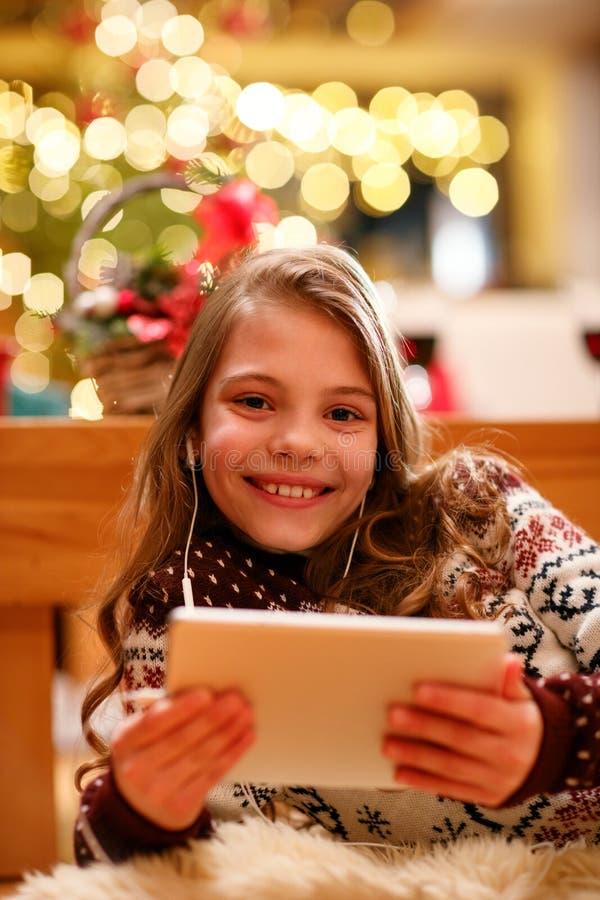 Porträt des netten Mädchens mit Tablette und Kopfhörern zu Hause stockbild