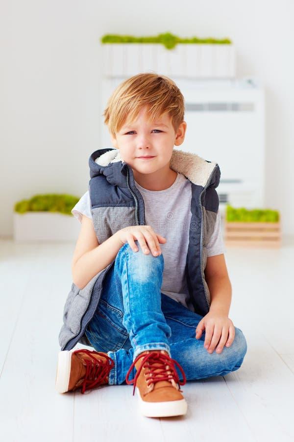Porträt des netten modernen Kindes, Junge, der auf dem Boden sitzt lizenzfreies stockfoto