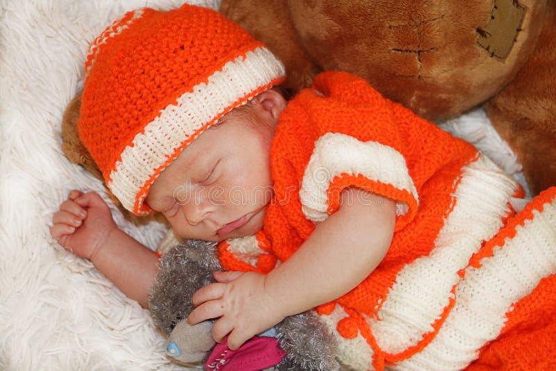 Porträt des netten neugeborenen Babys im orange Kostüm schlafend auf Whit lizenzfreies stockbild