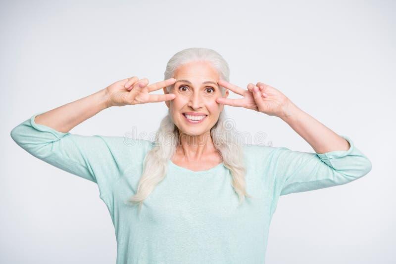 Porträt des netten Rentners Vzeichen nahe ihrer lächelnden tragenden Türkisstrickjacke des Gesichtes machend lokalisiert über wei lizenzfreies stockfoto