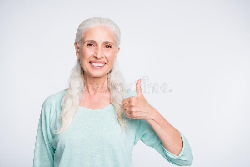 Porträt des netten Rentnervertretungsdaumens herauf den empfehlenden tragenden Türkispullover des Promo lokalisiert über weißem H stockfoto