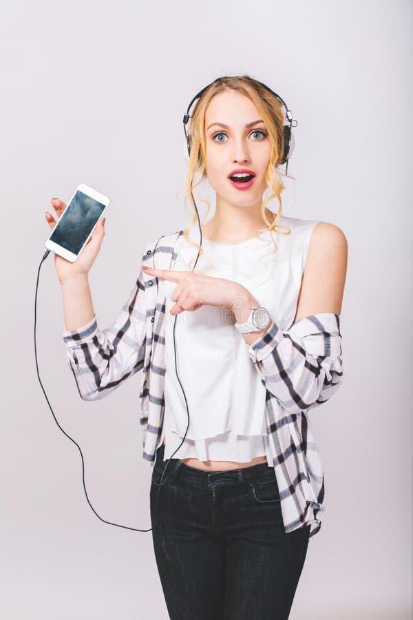 Porträt des netten schönen blonden Mädchens mit dem überraschten Gesicht, das auf grauem Hintergrund, Kamera betrachtend aufwirft lizenzfreies stockfoto