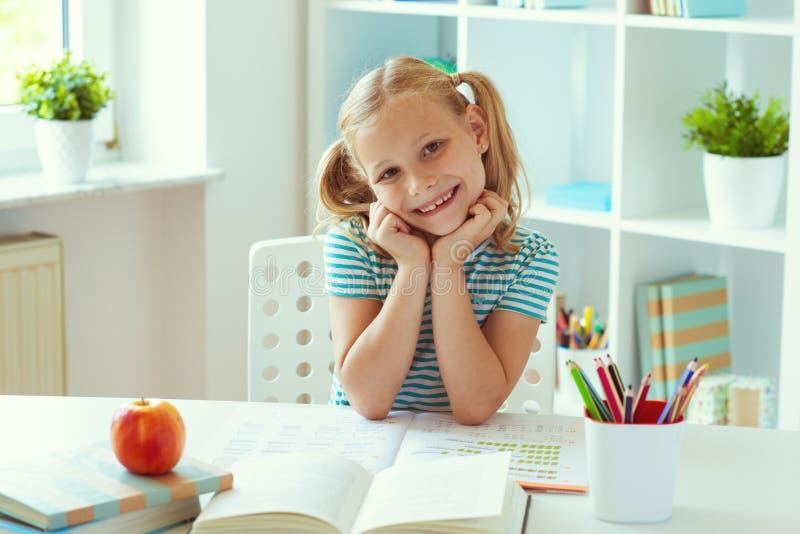 Porträt des netten Schulmädchens, das am weißen Tisch am hellen Klassenzimmer sitzt lizenzfreies stockfoto
