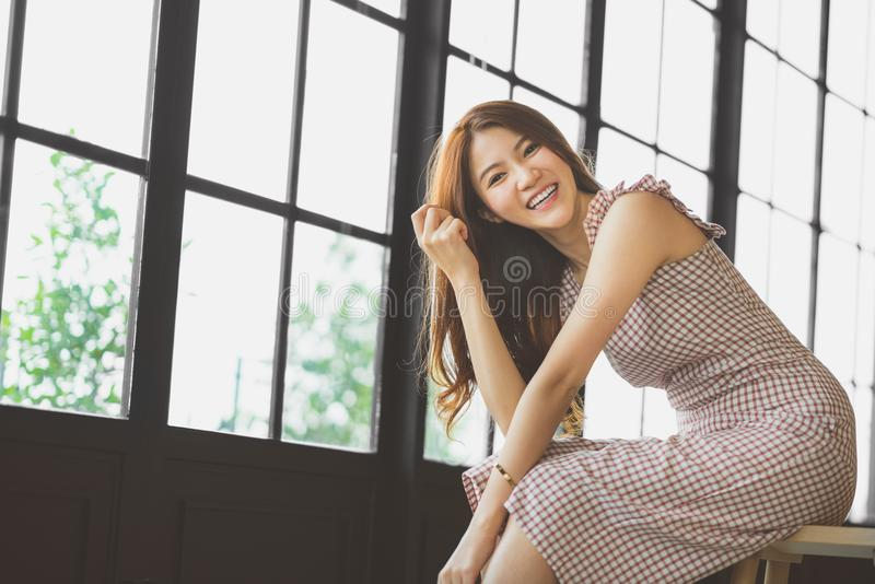 Porträt des netten und schönen asiatischen Mädchens, das in der Kaffeestube oder im modernen Büro mit Kopienraum lächelt Glücklic stockbild
