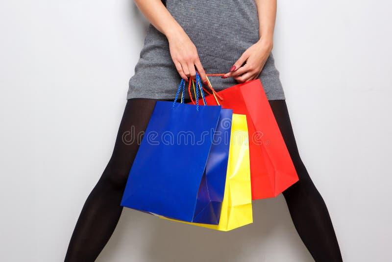 Porträt des niedrigen Winkels der weißen Frau bunte Papiergeschenktaschen halten lizenzfreie stockfotos